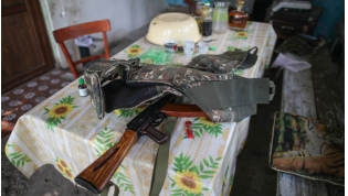 A bulletproof vest and an assault rifle are on the table in the yard of a house in Karabakh.